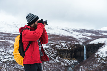 Man using camera in snowy landscape