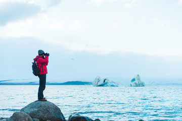 Man in warm clothes taking picture of lake