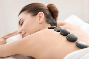 Young woman enjoying stone massage in spa salon
