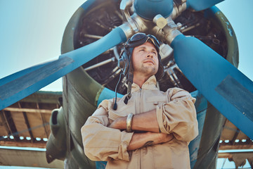 Valiant handsome pilot in a full flight gear standing with crossed arms near military airplane. Wall mural