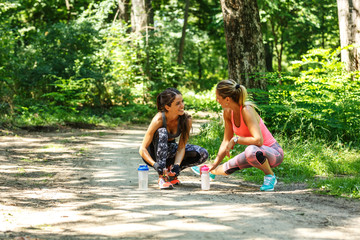 Two young woman stretching and relaxing after jogging outdoor.Green environment.
