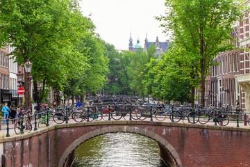 Gracht mit Fahrrädern und Brücke in Amsterdam