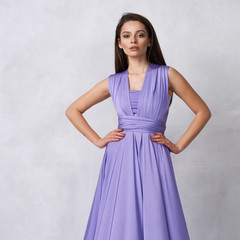 Beautiful long haired young woman dressed in stylish purple bandeau maxi dress posing against white wall on background. Elegant brunette female model demonstrating evening outfit in studio.