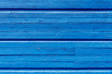 Texture. Old painted wall of the house. Old wooden fence. Blue paint.