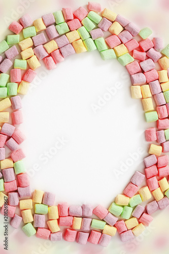 Border from bright colorful marshmallow on white background