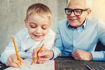 Easy numbers. Friendly smiling grandfather doing interesting exercises with his clever little boy