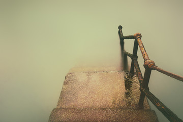 rusty handrail going down on water with vintage effect