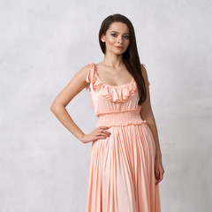 Full body portrait of gorgeous young brunette woman dressed in exquisite nude ball gown with lace top. Attractive female model in elegant dress posing against white wall on background.