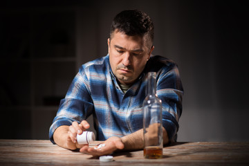 depression, drug abuse and addiction people concept - unhappy drunk man with bottle of alcohol and pills committing suicide by overdosing on medication at night