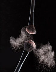 Brush for makeup with flying around powder is isolated on a black background