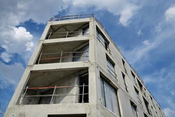 Immeubles en cours de construction, béton brut et ciel bleu.