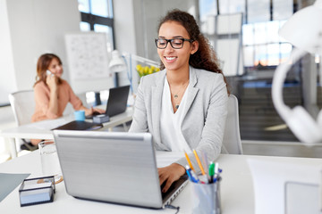 business, technology and people concept - smiling businesswoman in glasses with laptop computer working at office