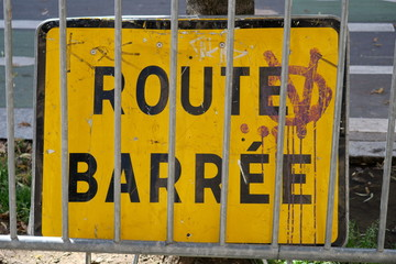 Route barrée, panneau derrière une barrière.
