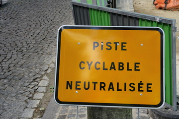 Piste cyclable neutralisée. rue, panneau jaune, lettres noires.