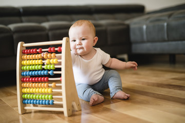 Adorable toddler girl playing with a colorful pyramid