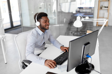 business, technology and people concept - happy african american businessman with headphones and computer listening to music at office
