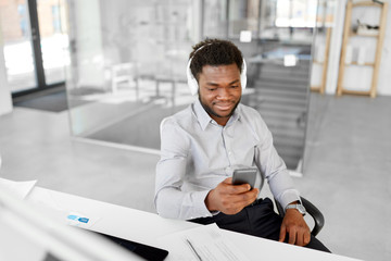 business, technology and people concept - happy african american businessman with headphones and smartphone listening to music at office