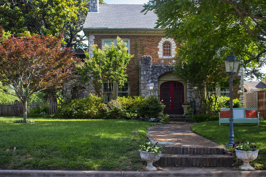 Beautiful upscale house with rock castle like entrance and retro metal lounger  and little rabbit in front yard - curb appeal