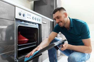 household and people concept - man wiping table with cloth cleaning oven door at home kitchen