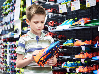 Boy with football boots in sport store