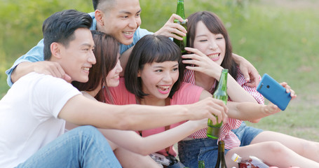 Young friends taking selfie on mobile phone in the park when going picnic