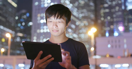 Man use of tablet computer at outdoor in the evening