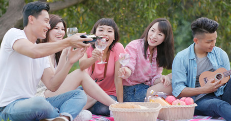 Asian Young friends enjoy the picnic time in the park