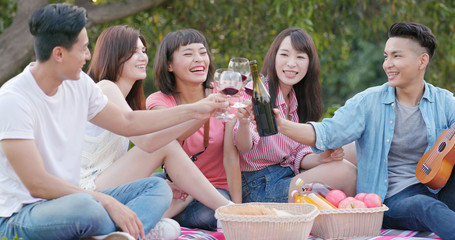 Friends go picnic together in the park and enjoy the food and drink