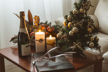 Christmas Decoration on the table with champagne, candles and glasses
