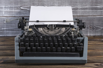 Vintage typewriter with a clean sheet of paper on an old wooden background