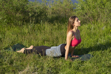 Young beautiful woman doing peacefully yoga outdoors