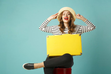 Young happy beautiful woman in summer hat holding yellow suitcase over blue background
