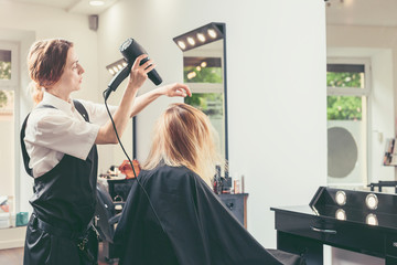 Beautician blow dry woman's hair at beauty salon