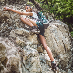 Young woman free climbing on a rocky mountain