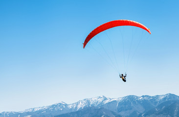 Photo sur Aluminium Aerien Sportsman on red paraglider soaring over the snowy mountain peaks