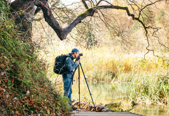Professional Nature photographer using a tripod takes a shot of the autumn lakes in Plitvice Lakes National Park, Croatia.