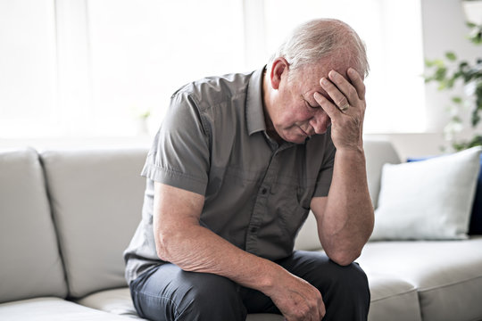 senior man thinking and sitting on sofa at home like sad