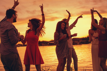 Group of young people have a party by the river during the sunset