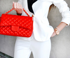 Business woman lady style.Fashionable and luxury style elegant red leather female bag. Elegant woman in white  suit holding small red leather bag with golden detail .Stylish accessories
