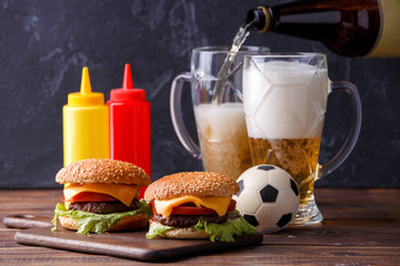 Image of two hamburgers, glasses, soccer ball, ketchup