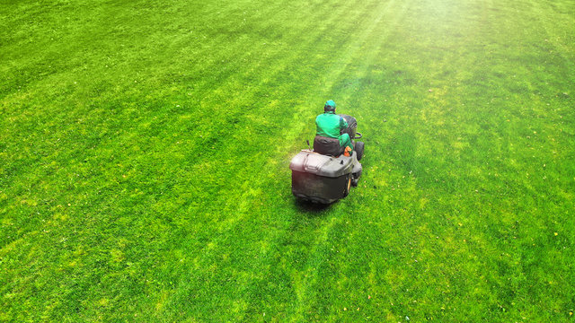 Lawnmower with worker. Grass cutting background.