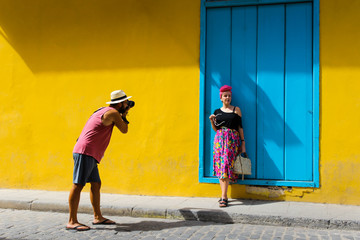 Wall Murals Havana Man taking a photo of a girl against a yellow wall
