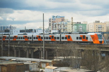 Russian train against the background of high-rise buildings in St. Petersburg.