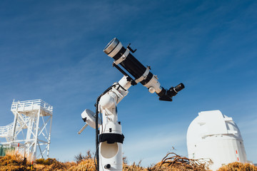 astronomical telescope tube, dome building and blue sky background