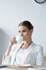 attractive young businesswoman drinking coffee at office