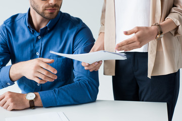 cropped shot of businessman sitting at workplace while his colleague passing documents to him isolated on white