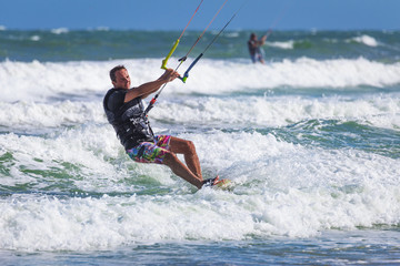 Young athletic man riding kite surf on a sea