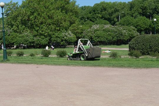 Naked european man is riding green lawnmower.