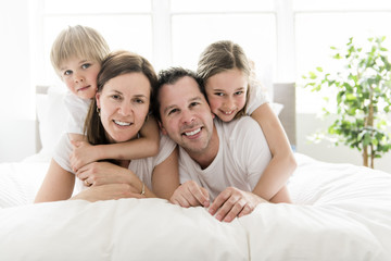 Family of four having fun on the bed at home