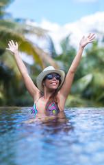 Young slim brunette woman sunbathe in tropical swimming pool